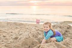 Ung flicka som plaskar och kastar bollen i sjön royaltyfria foton