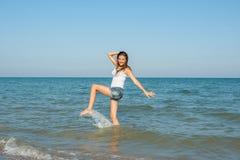Ung flicka som plaskar vattnet i havet Arkivfoto