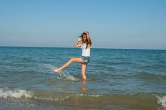 Ung flicka som plaskar vattnet i havet Arkivbild