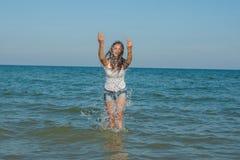 Ung flicka som plaskar vattnet i havet Royaltyfria Bilder