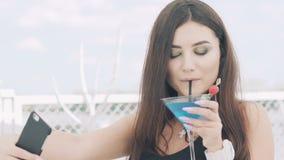 Ung flicka som poserar för selfie med bägaren av den blåa coctailen på pir stock video