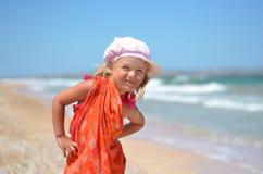 Ung flicka som poserar i orange klänning på stranden Arkivbild
