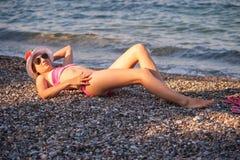 Ung flicka som poserar på stranden med hatten Royaltyfri Foto