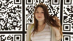 Ung flicka som poserar vid väggen med QR-kod lager videofilmer
