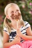Ung flicka som räknas i choklad som slickar skeden Arkivfoton
