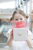Ung flicka som räcker gåva in mot kamera Arkivbild