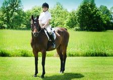 Ung flicka som rider en häst Royaltyfria Bilder