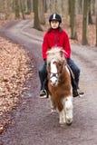Ung flicka som rider en ponny Royaltyfri Fotografi