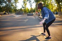 Ung flicka som rider en skateboard skateboarding Utomhus livsstil Arkivfoto