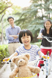 Ung flicka som rider hennes cykel med hennes familj Arkivfoto