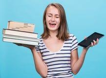 Ung flicka som rymmer en bok i en hand och enPC i det oth Royaltyfria Bilder