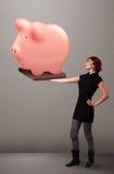 Ung flicka som rymmer en enorm besparingspargris Arkivbild