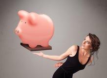 Ung flicka som rymmer en enorm besparingspargris Royaltyfri Foto