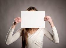 Ung flicka som rymmer ett tomt baner royaltyfria bilder