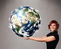 Ung flicka som rymmer jord för planet 3d Royaltyfri Foto