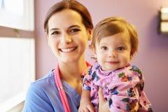Ung flicka som rymms av den kvinnliga pediatriska sjuksköterskan Royaltyfri Fotografi