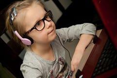 Ung flicka som ser bärbar datorskärmen Arkivfoto