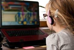 Ung flicka som ser bärbar datorskärmen Arkivfoton