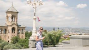 Ung flicka som ser domkyrkan för helig Treenighet av Tbilisi Tsminda Sameba - Georgia arkivfilmer