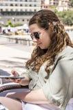 Ung flicka som ser hennes mobiltelefon på en vårdag arkivbilder