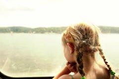 Ung flicka som ser till och med ett fartygfönster Royaltyfri Fotografi