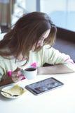 Ung flicka som sitter i ett kafé med koppen kaffe Royaltyfri Fotografi