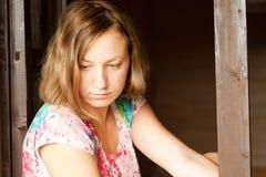 Ung flicka som sitter nära fönster Fotografering för Bildbyråer