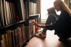 Ung flicka som sitter på golvet i arkiv mellan bokhyllor, läseböcker arkivbilder