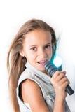 Ung flicka som sjunger med mikrofonen Fotografering för Bildbyråer