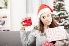 Ung flicka som skakar julgåvan Arkivfoton