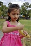 Ung flicka som skalar en stor banan. Royaltyfri Fotografi