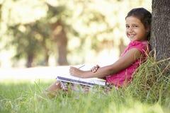 Ung flicka som skissar i bygdbenägenhet mot träd Royaltyfri Fotografi