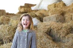 Ung flicka som skrattar på lantgård Royaltyfri Bild