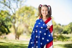 Ung flicka som slås in i amerikanska flaggan Arkivbild