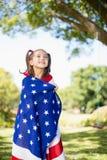 Ung flicka som slås in i amerikanska flaggan Fotografering för Bildbyråer