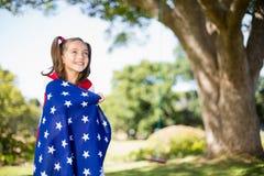 Ung flicka som slås in i amerikanska flaggan Royaltyfria Bilder