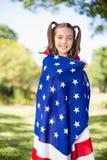 Ung flicka som slås in i amerikanska flaggan Arkivfoton