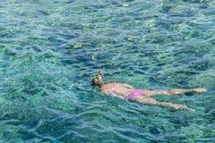 Ung flicka som snorklar i tropiskt vatten på semester Kvinnasimning i det blåa havet Snorkla flickan i rakt framifrån snorkla mas arkivbild