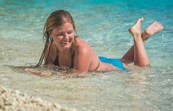 Ung flicka som solbadar i havsvatten som plaskar runt om henne Arkivbild