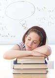 Ung flicka som sovar på böcker på skolan Arkivfoto