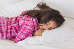 Ung flicka som sover i säng Royaltyfria Foton