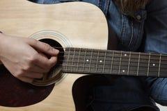 Ung flicka som spelar den akustiska gitarren med jeansskjortan Fotografering för Bildbyråer