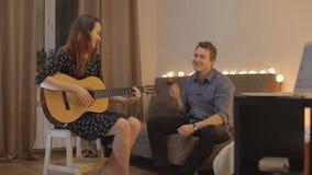 Ung flicka som spelar gitarren, grabben på maracasna arkivfilmer