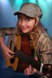 Ung flicka som spelar gitarren på etappen Fotografering för Bildbyråer