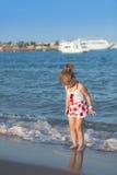 Ung flicka som spelar i havsvågor Royaltyfria Foton