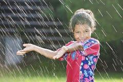 Ung flicka som spelar i regnet Arkivbilder