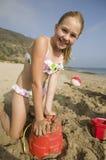Ung flicka som spelar i sand på stranden royaltyfria bilder
