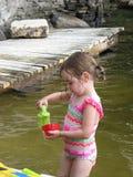 Ung flicka som spelar i sjön Royaltyfri Foto