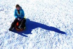 Ung flicka som spelar i snön som Sledding på fryst jordning Arkivbild