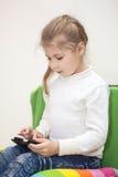 Ung flicka som spelar leken på mobiltelefonen som inomhus sitter Arkivbild